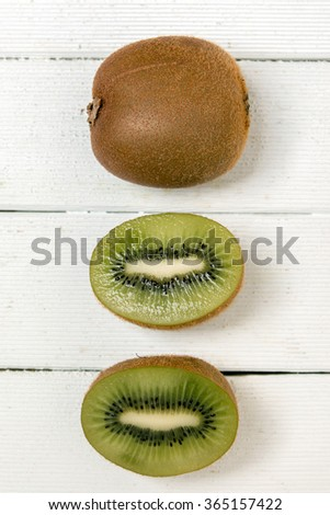 Close view of tasty kiwi fruits isolated on a white wooden background. - stock photo