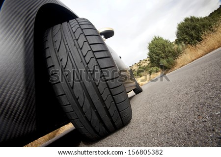 Close view of the wheel of a black sport car with the asphalt at foreground. Tire.