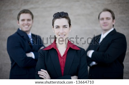 close view of three businesspeople standing with arms crossed in formal wear all smiling and looking at camera - stock photo