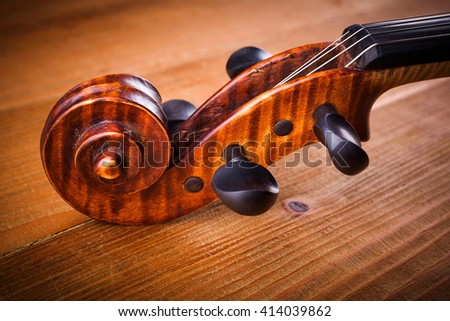 Close view of violin scroll and pegbox on wooden background