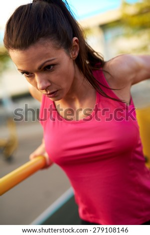 Close view of woman concentrating while doing triceps dips on a dip stand outside. - stock photo