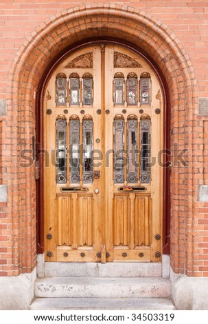 Closed antique wooden and glass door in red brick building - stock photo