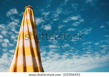 Closed beach umbrella with yellow lines against a blue sky with clouds - stock photo