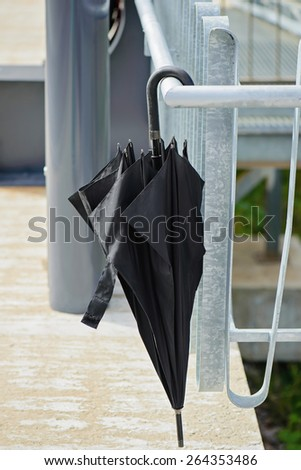 Closed black umbrella hanging on the railing outside - stock photo