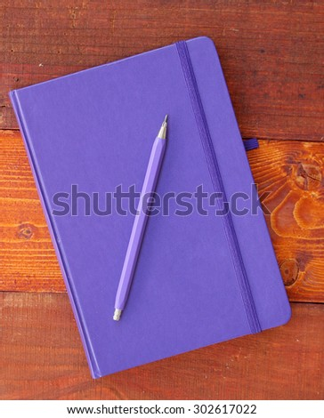 Closed blue notebook and pencil on wooden background - stock photo