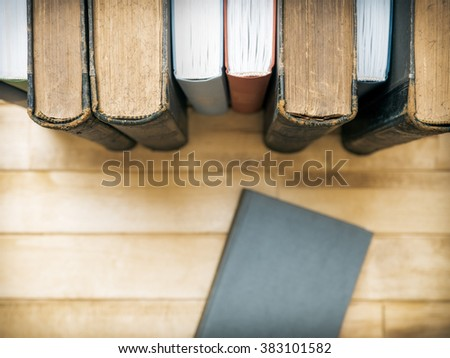 Closed book in front of several books on the table. Top view. Selective focus - stock photo