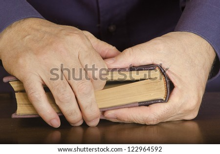 Closed book in the hands of a mature man. Selective focus on the edge of book and page edges. All other in soft focus