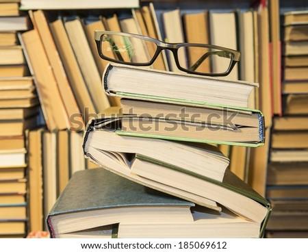 closed books, lying up against bookshelf background with black reading glasses - stock photo