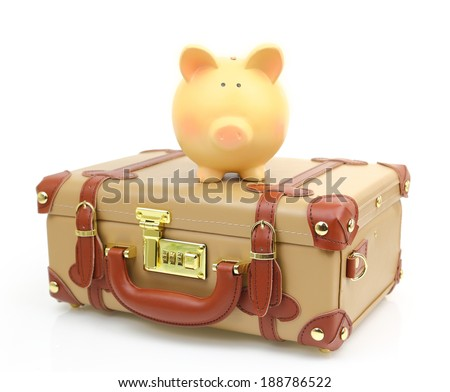 Closed brown suitcase with piggy bank on top of it - stock photo