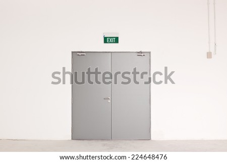 Closed door with an exit sign  - stock photo