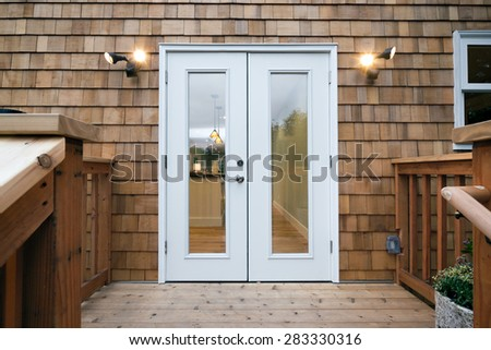 Closed double patio french doors with window at twilight in craftsman home.  - stock photo