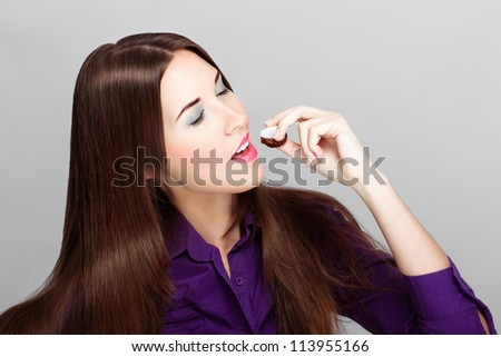 Closed eyes brunette woman eating sweetie - stock photo