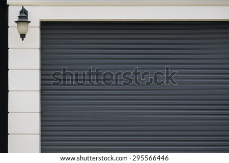 Closed garage gray gate and part of the walls of the house - stock photo