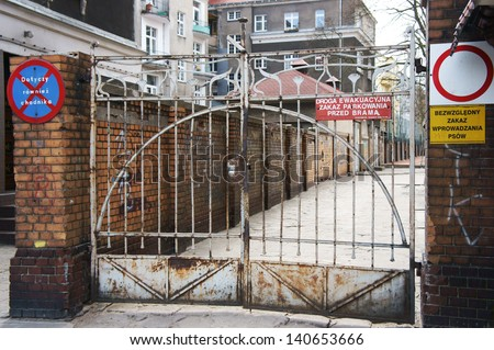 Closed gate with some warning signs - stock photo