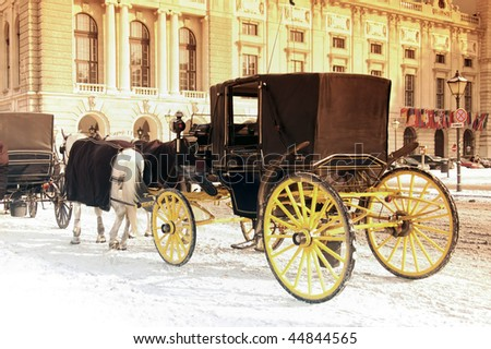 Closed horse coach with yellow wheels waits in the winter. - stock photo