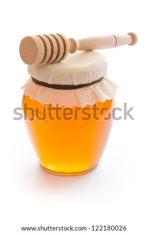 Closed jar of honey and stick isolated on white background - stock photo