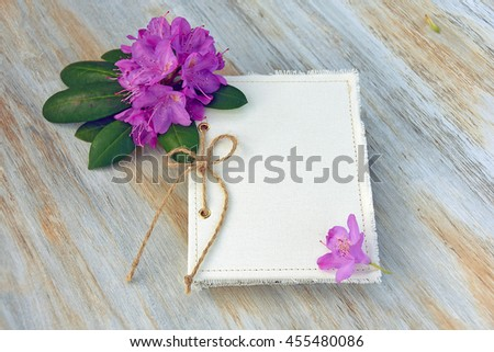 closed journal with twine bow and rhododendron blossom on weathered wood - stock photo