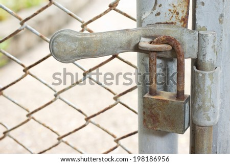 Closed lock with a chain on an old metal fence - stock photo