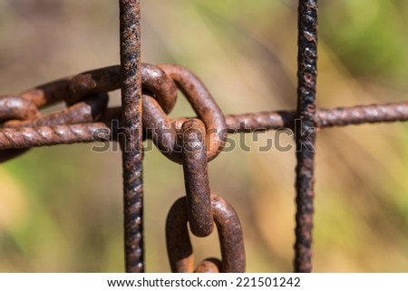 Closed lock with a rusty chain on an old metal fence - stock photo