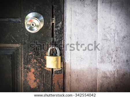 Closed metal lock to the old wooden door for security protection  with copy space - stock photo