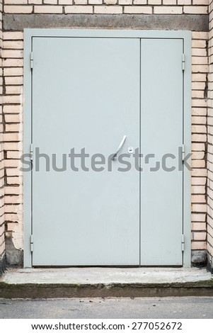Closed modern gray metal door in a brick wall, background photo texture - stock photo