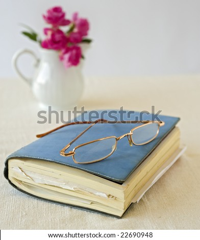 closed notebook and old glasses - stock photo