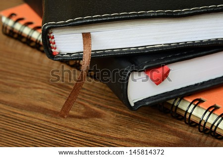 Closed notebooks on wooden table