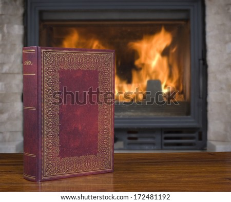 Closed old book with blank hardcover on the table and fireplace in the background - stock photo