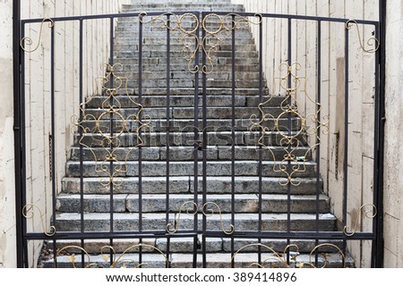 Closed on hinged gate lock with forged elements on the background of the stone stairs. - stock photo
