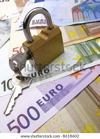closed padlock with keys on  background euro and dollar banknotes, close up
