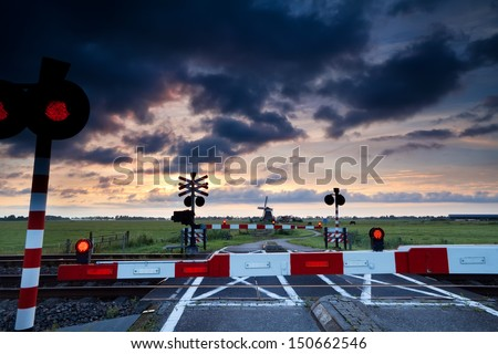closed rail crossing with red signals at sunrise and windmill - stock photo