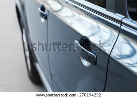 Closed rear door handle. Modern blue car closeup fragment with shallow DOF and selective focus - stock photo