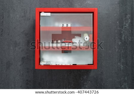 Closed red metal medical care box full of drugs hanging on a dark gray marble wall background. Front view