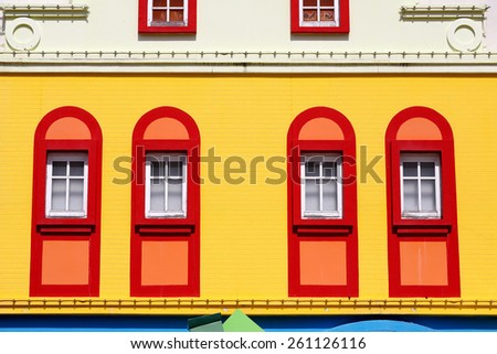 Closed red window on colorful yellow wall - stock photo