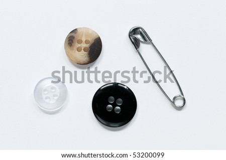 Closed safety pin and white, black and borown buttons in white background - stock photo