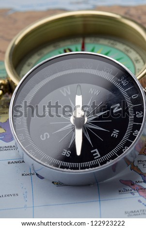 Closed shot of a compass on top of map - stock photo