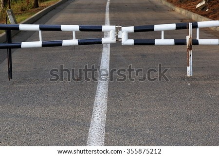 Closed striped road barrier on the way at evening
