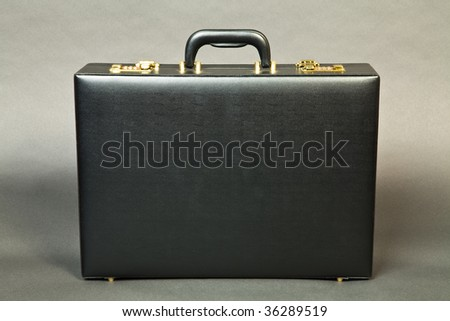 Closed suitcase on a dark background
