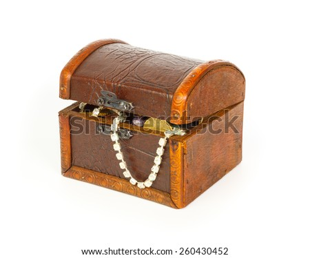Closed treasure chest with bracelet, coins and pearls against white background