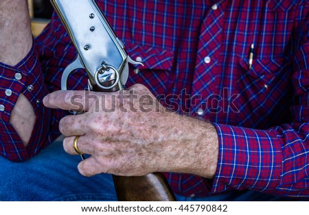 Closed up a hand of senior man  holding rifle gun  - stock photo