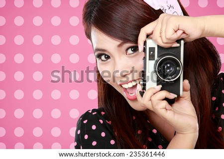 Closed up Beautiful woman in action with vintage camera over polka dot pink background