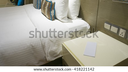 Closed up blank note on side table at king sized bed in a business hotel room at night