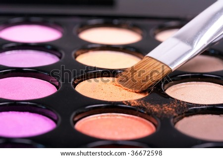 Closed-up eyeshadows with professional make-up brush - stock photo