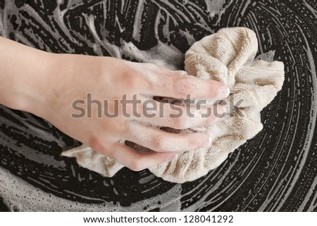 Closed up female hand using soapy rag to wipe a ceramic furniture - stock photo