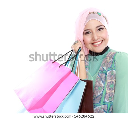 Closed up of happy young muslim woman with shopping bag isolated over white background - stock photo