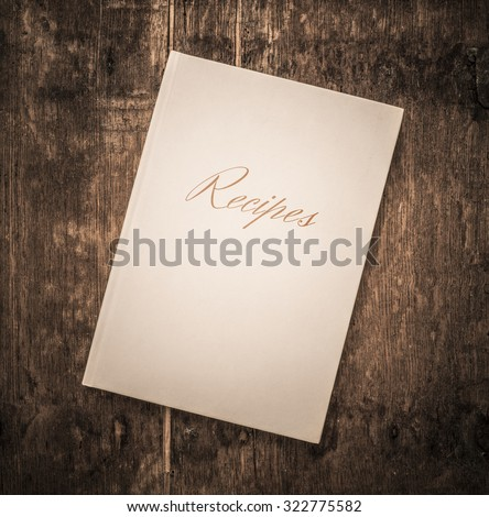 Closed white book with the title Recipes on wooden surface. Empty space for copy or to use as mock-up.