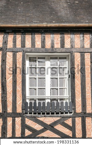 Closed window of timber frame building with red brick texture wall in Beuvron en Auge, Nomandy, France - stock photo
