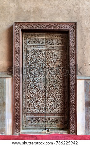 Closed wooden aged door with ornate bronzed geometric patterns, Cairo, Egypt