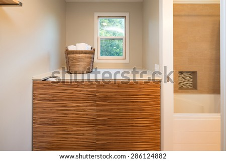 Closed wooden closet for washer and dryer with towel basket.  - stock photo