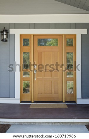 Closed wooden front door of a home with gray panels in daytime. - stock photo